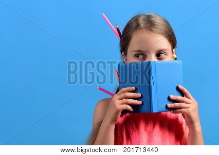 Kid In Pink Blouse With Colored Pencils In Hair
