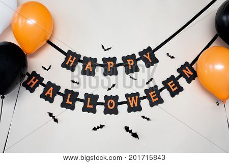 holidays, decoration and party concept - happy halloween festive paper black garland or banner with air balloons and bats over white background