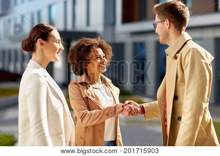 business, partnership, gesture and cooperation concept - happy people shaking hands on city street