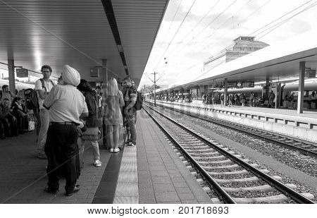 MANNHEIM GERMANY - AUG 8 2017: Large group of people including Indian tourist wearing turban waiting at the train station platform in Mannheim hauptbahnhof Train station commuting in German