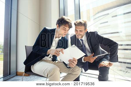 Mature businessman using a digital tablet to discuss information with a younger colleague in a modern business office
