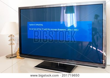 Update install process of system update software process on a modern television set in living room with message System is initializing do not turn TV
