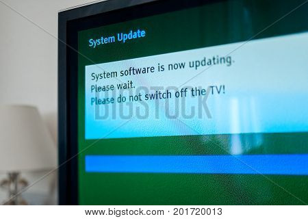 System update software process on a modern television set in living room with message System software is now updating please wait. Please do not switch off your tv. Tilt-shift lens used