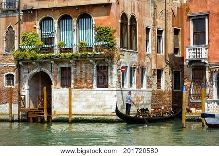 Venice, Italy - May 18, 2017: The gondola with tourists floats along the Grand Canal. Gondola is the most attractive tourist transport in Venice
