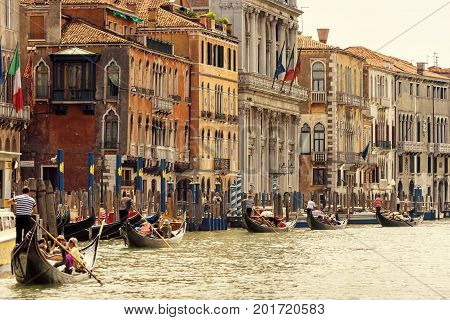 Venice, Italy - May 18, 2017: Gondolas with tourists are sailing along the Grand Canal the main street of the city. Gondola is the most attractive tourist transport in Venice.