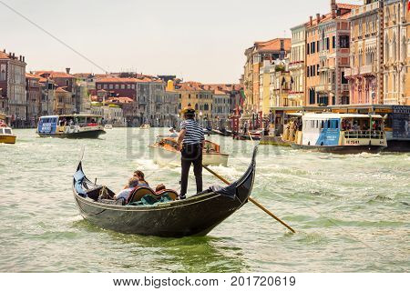 Venice, Italy - May 18, 2017: Gondola and other tourist boats are sailing along the Grand Canal. Grand Canal is one of the major water-traffic corridors in Venice.