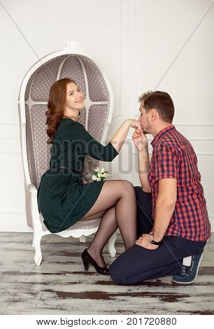 Man kisses woman's hand while she is sitting in armchair.