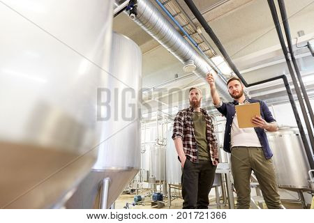 manufacture, business and people concept - men with clipboard working at brewery or non-alcoholic beer production plant
