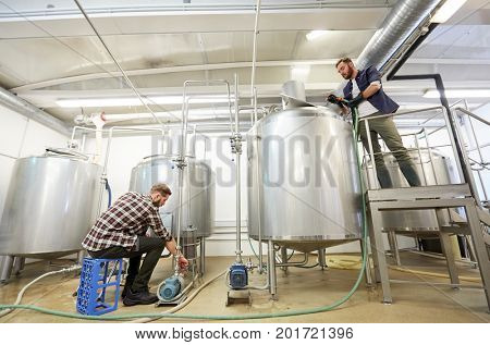 production, business and people concept - men working with kettles and compressors at craft beer brewery or non-alcoholic beverage plant