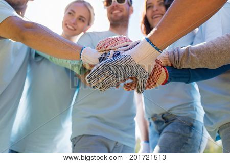 volunteering, charity, people, gesture and ecology concept - group of volunteers putting hands on top in park