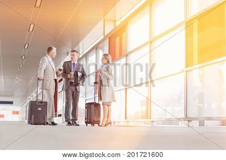 Full length of businesspeople with luggage talking on railroad platform