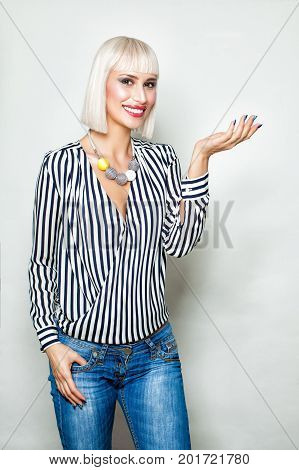 Smiling Woman Showing Empty Copy Space on the Open Hand. Empty Hand Fashion Makeup Blonde Hair