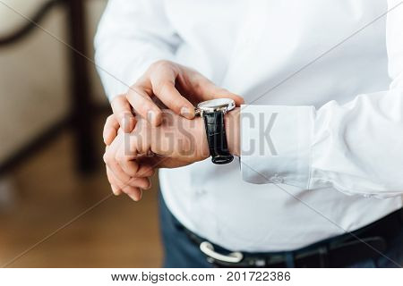 Fat groom clasping stylish watch band on his wrist.