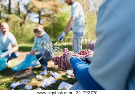 volunteering, people and ecology concept - volunteer woman with garbage bag and plastic bottle cleaning area in park