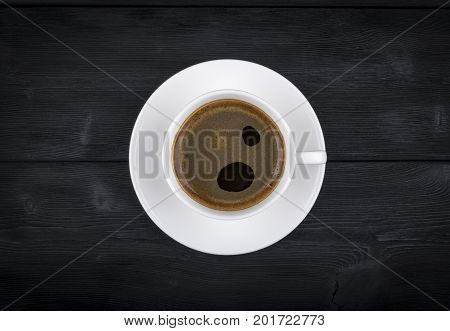 Overhead view of a freshly brewed mug of espresso coffee on black rustic wooden background with woodgrain texture. Coffee break style concept