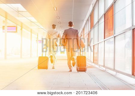 Full length rear view of businessmen with luggage running on railroad platform