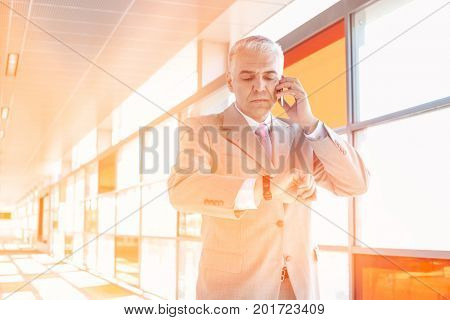 Middle aged businessman checking time while on call at railroad station