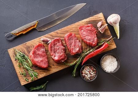 Raw filet mignon steaks with herbs and spices. Modern restaurant cuisine still life with organic beef and flavotings, chef knife on wooden board at black background, copy space, top view