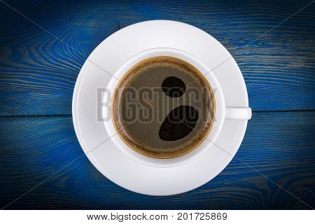 Overhead view of a freshly brewed mug of espresso coffee on blue rustic wooden background with woodgrain texture. Coffee break style concept