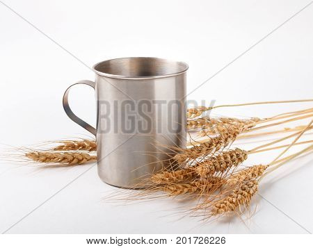 ripe wheat spikelets and metal mug on empty white background