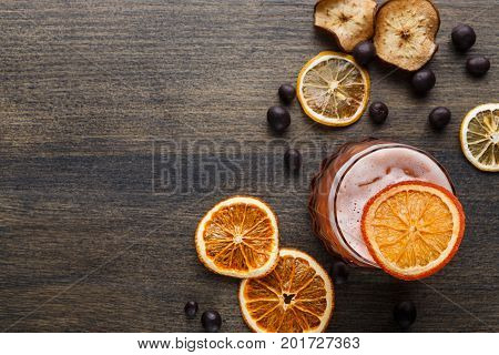 Cocktail on rustic wood background. Cold citrus alcohol beverage with tequila, blood orange juice and ginger beer, served with ice, citrons and chocolate snacks, top view, copy space