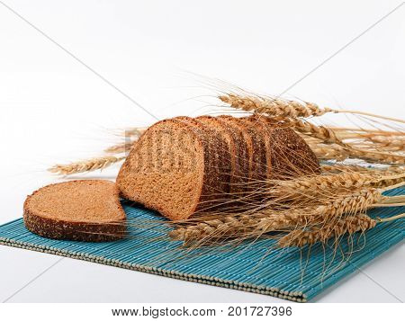 bread slices and wheat spikelets on bamboo mat. selective focus