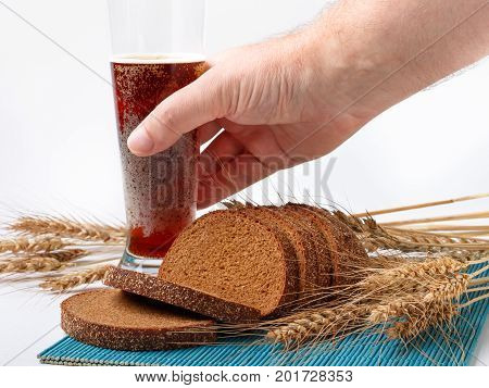 sliced bread and wheat spikelets on bamboo mat with hand holding glass of soft drink. selective focus