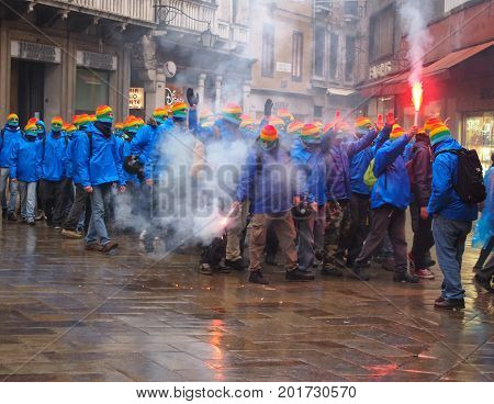 Venice March 03 2015: anti capitalist demonstrators on the streets in venice with masks and flares with smoke