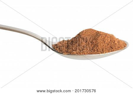 Nutmeg powder in spoon. Isolated in white background