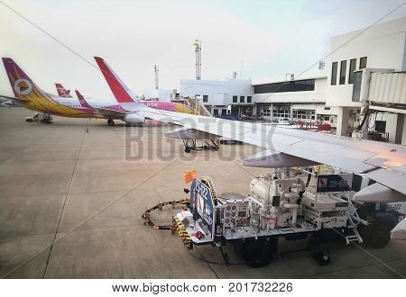 BANGKOK, THAILAND - MAY 20, 2017: Don Mueang International Airport activities - aircraft refueling operation; mini-truck parking beside Nok Air airplane; many planes waiting for boarding at gates, etc.