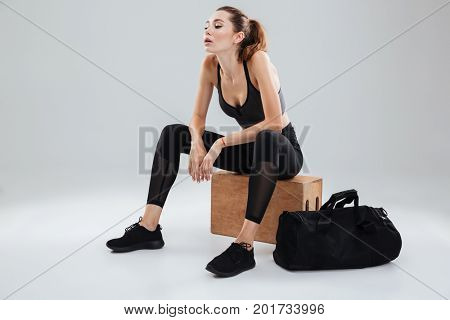 Tired Awesome Sport woman relaxing on box in studio over gray background