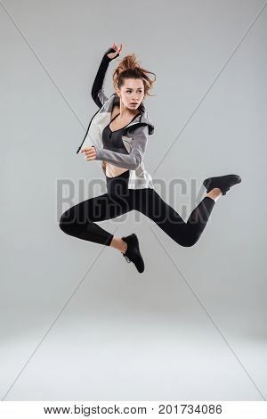 Full length portrait of a young healthy woman in sportswear jumping and looking away isolated over gray background