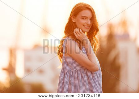 Beauty Young Ginger girl in dress posing sideways on the sunset and looking at the camera