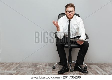 Displeased frustrated businessman in eyeglasses holding pc tablet while sitting in chair and gesturing with hand isolated over gray background