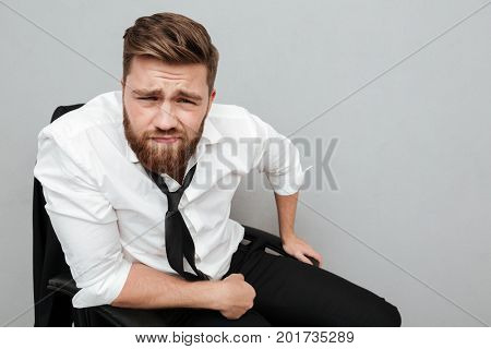 Close up portrait of a young frowning man in white shirt staring at camera while sitting in chair isolated over gray background
