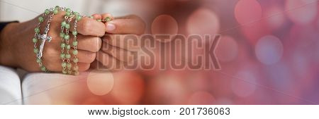 Digital composite of Hands with rosary on bible and red bokeh transition