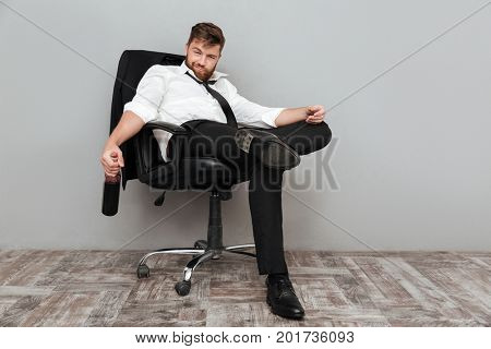 Happy drunk businessman sitting in office chair with bottle of wine isolated over gray background