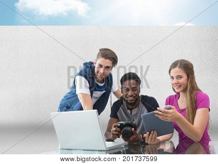 Digital composite of Group of people on laptop with camera in front of grey background with sky