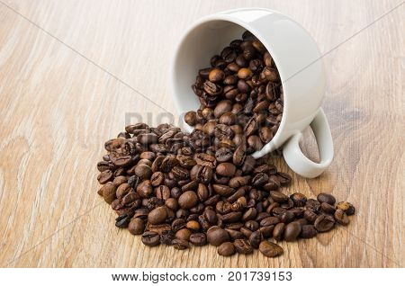 Overturned Cup And Scattered Coffee Beans On Table