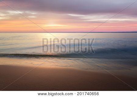 calm water on a background quiet sunset / wild beach dawn alone