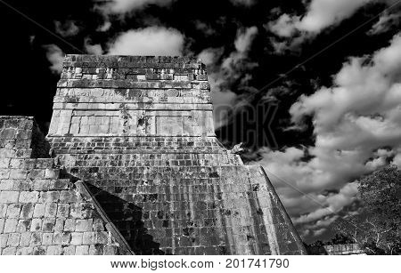 A magnificent image of the Temple of the Jaguar warriors in Chichen Itza adjoining the ball game Yucatan. Mexico.white and black dark sky and clouds daylight