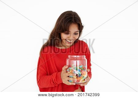 Portrait of excited pleased young Latin female wearing red casual sweater holding large glass jar with colorful sweets or marmalades having joyful and satisfied expressing on her pretty face