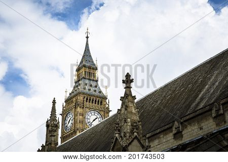 LONDON ENGLAND - JUNE 14 2016: Horinzontal picture with a partial view of the Big Ben with a part of the Parliament rooftop on the right on a cloudy day in London.