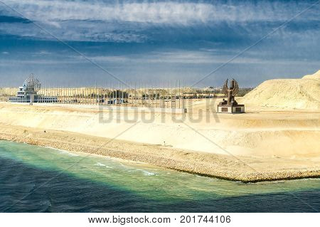 Sinai Egypt - April 2nd 2016: Section of the Suez Canal expansion canal opened in August 2015 with the Suez Canal monument government building in the form of a ship and the al-Sisi monument