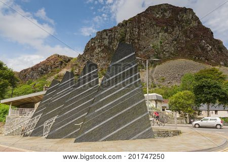 Blaenau Ffestiniog Wales UK - August 22 2017: Mountains towering above the Welsh town of Blaenau Ffestiniog with slate obelisks engraved with Welsh poetry to commemorate the town's mining past