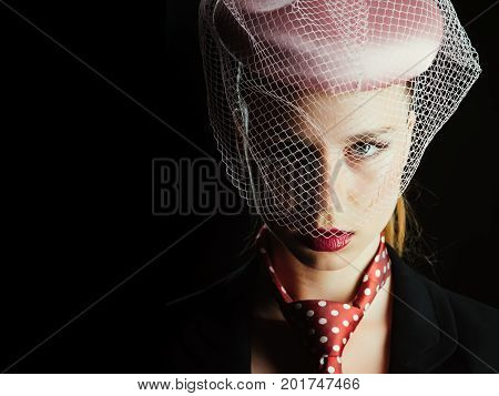 Girl in tie with red dots on neck. Retro or vintage style concept. Lady posing on black background. Fashion and accessories. Woman wearing pink hat with veil copy space