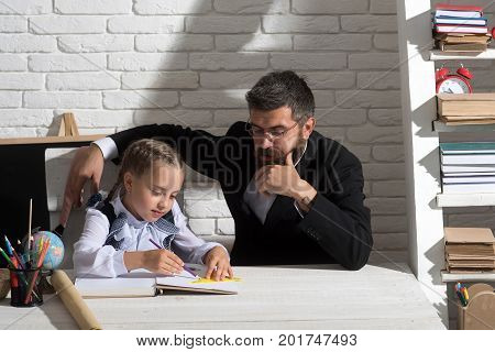 Schoolgirl And Her Dad With Thoughtful Faces Write In Notebook