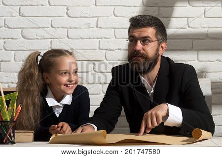 Girl And Man Sit At Desk, Read Map. Home Schooling