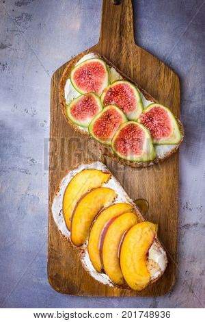 Toasted sandwiches with cream cheese topped with fresh ripe figs and peaches. Drizzled with honey. Wholegrain rye bran bread on wood cutting board grey concrete background