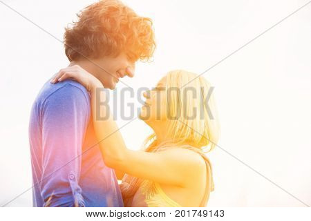 Romantic young couple looking at each other against clear sky